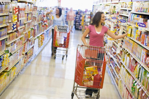 Two women shopping in supermarket grocery aisle